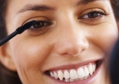 Closeup of cute woman applying mascara to her eyelashes, Maskara Bürste - Huber Bürsten
